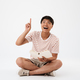 Portrait of a happy young asian man sitting with legs crossed - PhotoDune Item for Sale