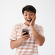 Portrait of an excited asian man looking at mobile phone - PhotoDune Item for Sale