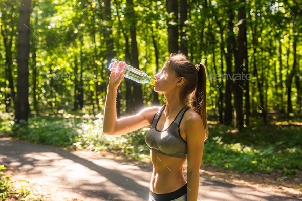 Young woman drinking water after jogging outdoors - Stock Photo - Images