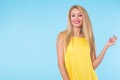 blonde woman with red lips and yellow dress on blue background with copy space - PhotoDune Item for Sale