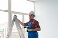 Happy male builder standing on ladder with drill infront of window. - PhotoDune Item for Sale