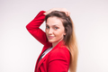 Young lady in red jacket corrects her hair on white background - PhotoDune Item for Sale
