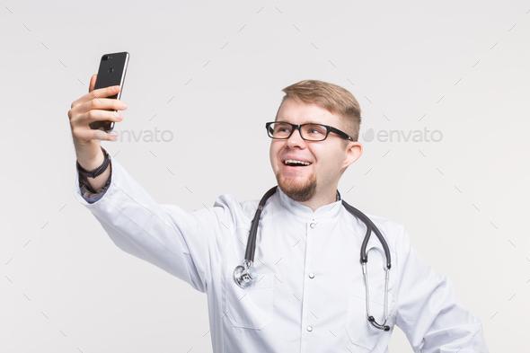 Happy male doctor making selfie in studio - Stock Photo - Images