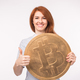 Red-haired woman holding big bitcoin and showing thumbs up  - PhotoDune Item for Sale