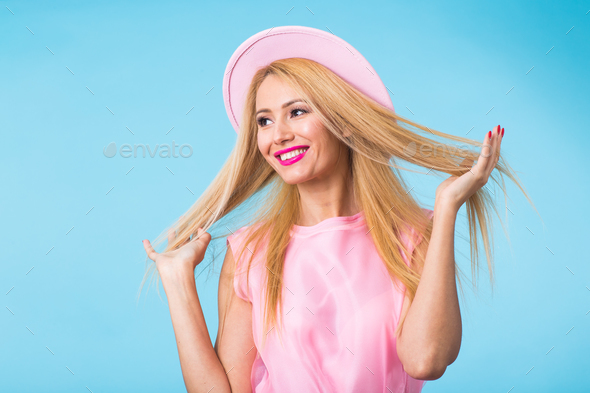 Portrait of smiling blonde woman in fashionable look on blue background - Stock Photo - Images