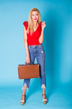 Summer, fashion and holiday concept - Beautiful blonde woman with retro suitcase on blue background - PhotoDune Item for Sale