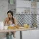 Young Asian Mother Holding Little Baby on the Knees, Sitting in the Kitchen. - VideoHive Item for Sale