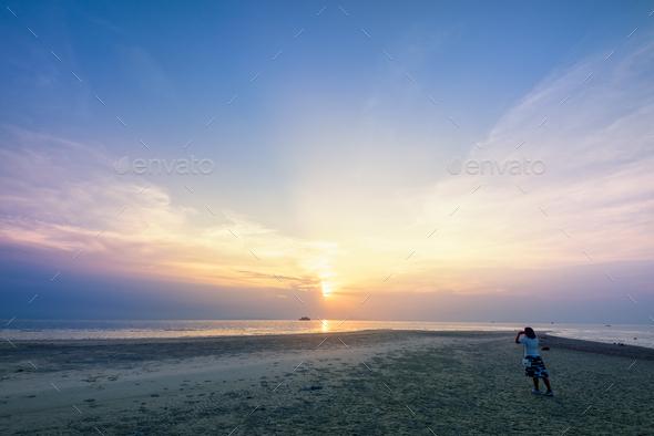 Woman tourist taking photo on the beach - Stock Photo - Images