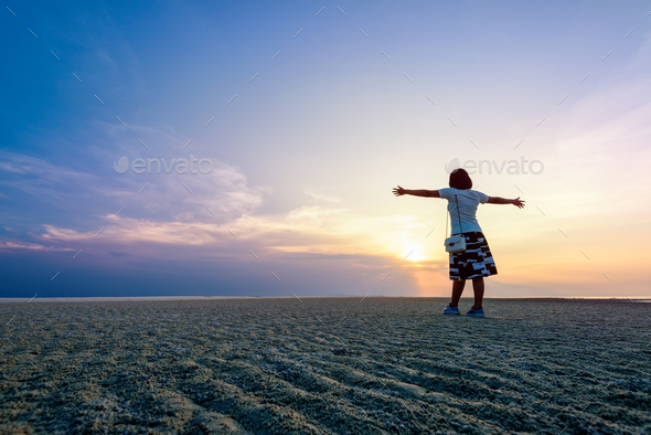 Woman standing arms outstretched at sunset - Stock Photo - Images