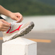 Woman tying shoelace his before starting running-4 - PhotoDune Item for Sale