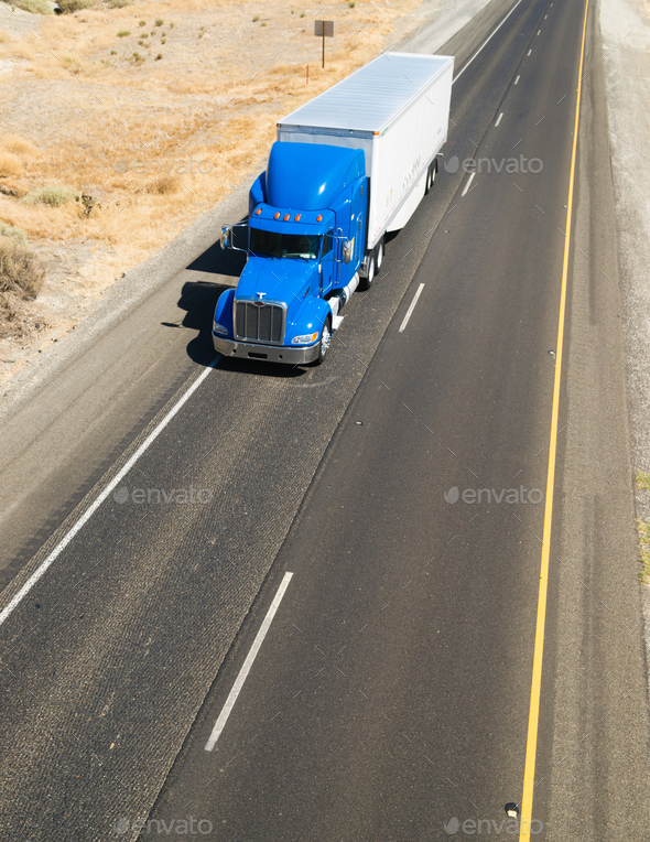 Big Blue Truck Hauling a Load of Freight down the Highway - Stock Photo - Images