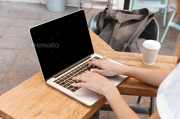 Cropped photo of caucasian woman sitting at table outdoor on sum - Stock Photo - Images