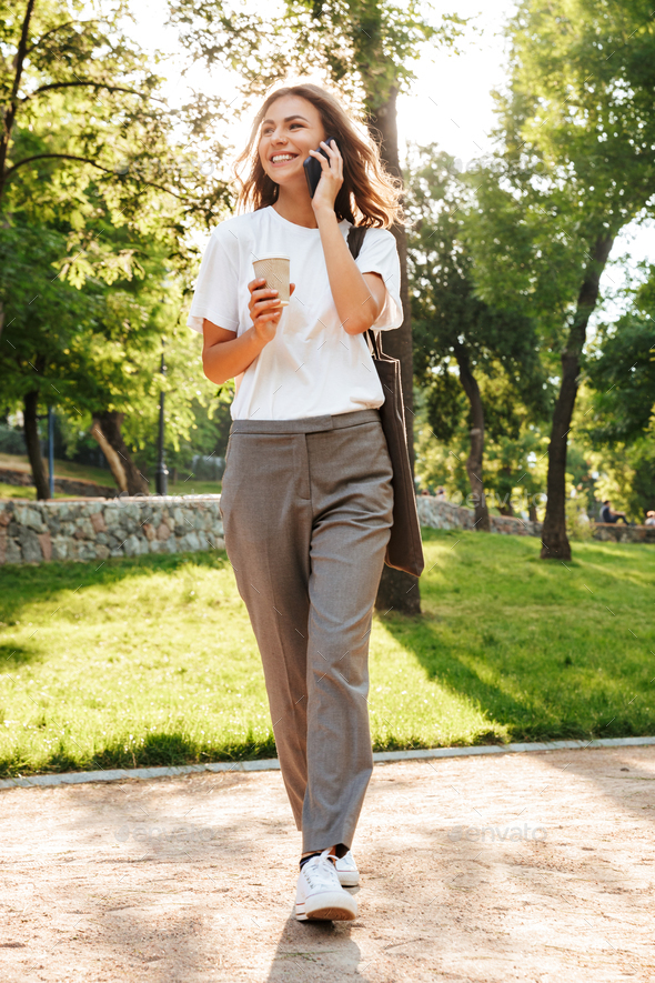 Full length image of caucasian smiling woman walking down narrow - Stock Photo - Images