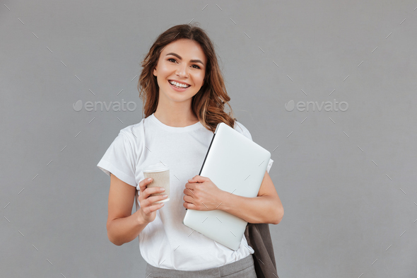 Image of beautiful young woman smiling and standing against gray - Stock Photo - Images
