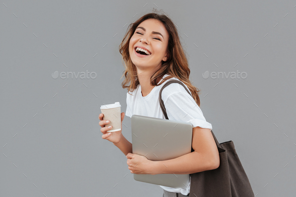 Image of happy young woman 20s laughing and standing over gray w - Stock Photo - Images