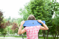 Happy girl holds a blue skateboard on her shoulders in the park - PhotoDune Item for Sale