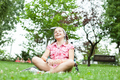 Happy teenager girl sitting on the grass - PhotoDune Item for Sale