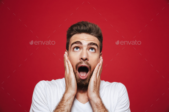 Portrait of an amazed young bearded man screaming loud - Stock Photo - Images