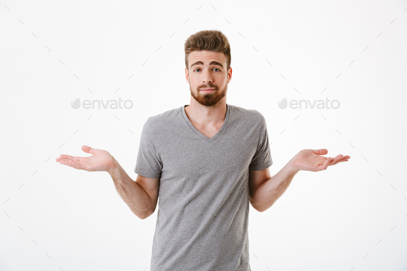 Confused young man standing isolated over white wall - Stock Photo - Images