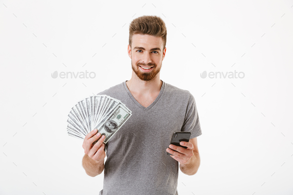 Man standing isolated using mobile phone holding money. Looking camera. - Stock Photo - Images