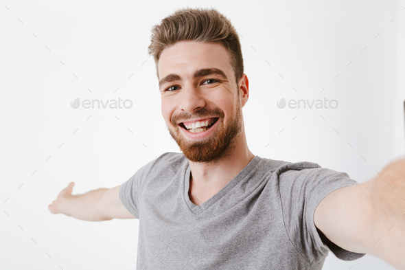 Portrait of a cheerful young bearded man taking a selfie - Stock Photo - Images
