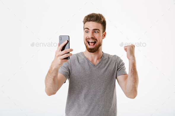 Excited young man using mobile phone make winner gesture. - Stock Photo - Images
