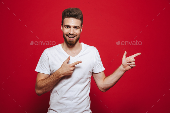 Handsome happy young man in white t-shirt pointing. - Stock Photo - Images