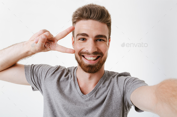 Portrait of a cheerful young bearded man showing peace - Stock Photo - Images