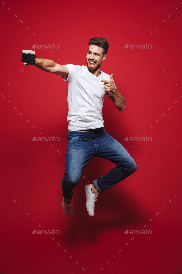 Full length portrait of a joyful young bearded man - Stock Photo - Images