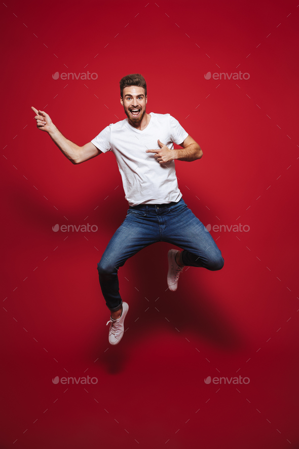 Full length portrait of a cheerful young bearded man - Stock Photo - Images