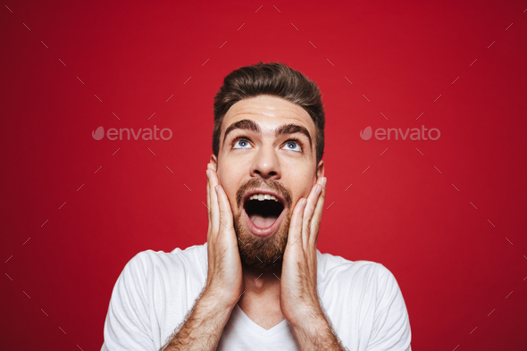 Portrait of an excited young bearded man screaming loud - Stock Photo - Images