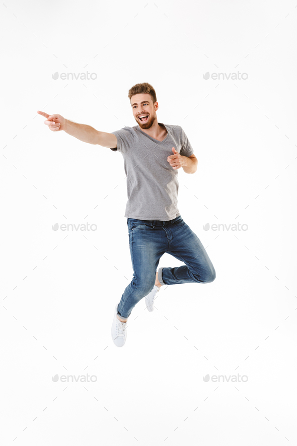 Emotional excited young man jumping isolated pointing. - Stock Photo - Images