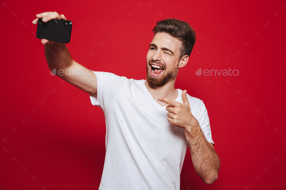 Portrait of a cheerful young bearded man pointing finger - Stock Photo - Images