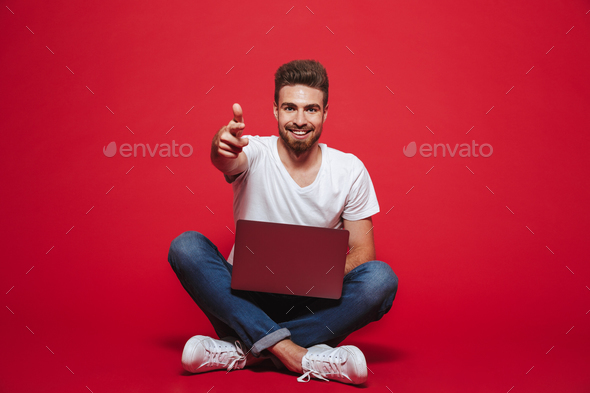 Portrait of a happy young bearded man pointing at camera - Stock Photo - Images