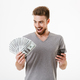 Happy young man using mobile phone holding money. - PhotoDune Item for Sale