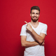 Handsome happy young man in white t-shirt pointing. - PhotoDune Item for Sale