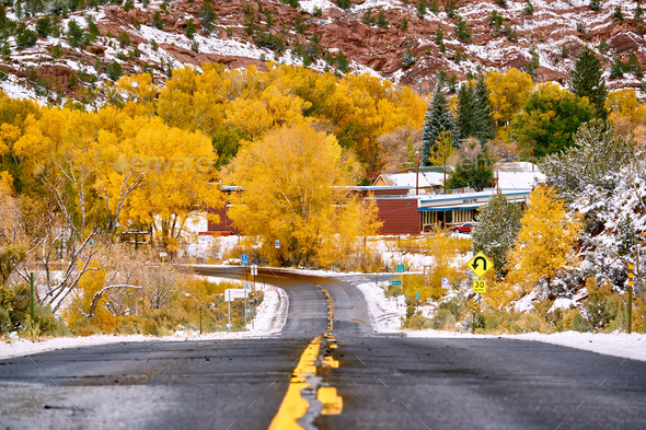 First snow and autumn trees along wet highway - Stock Photo - Images