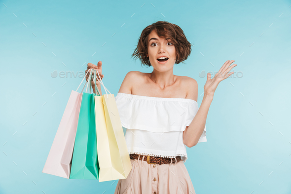 Portrait of an excited young woman showing shopping bags - Stock Photo - Images