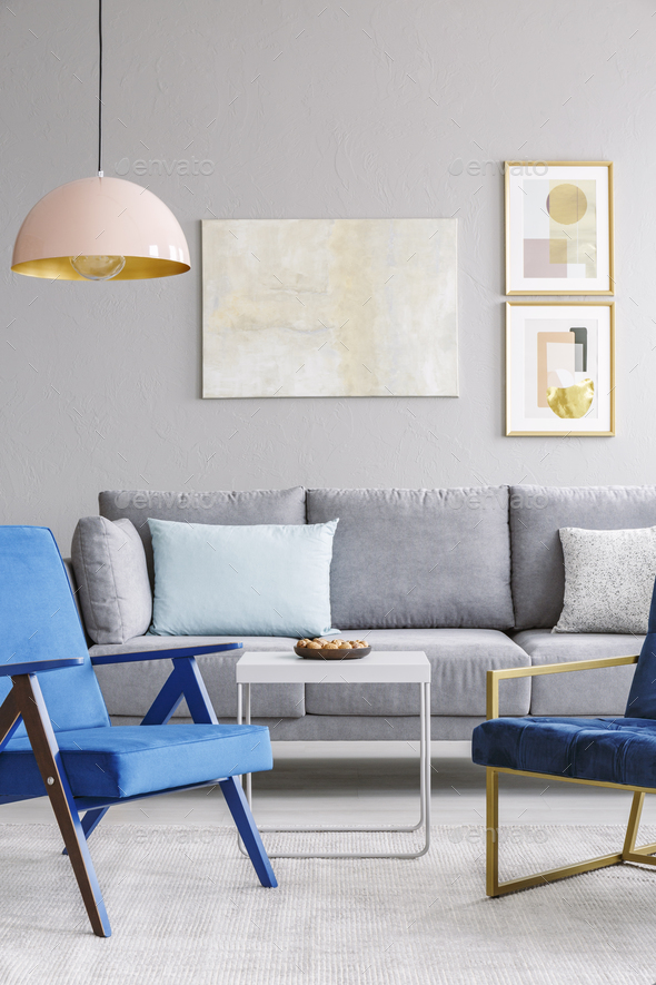 Real photo of two blue chairs standing in front of a grey couch - Stock Photo - Images