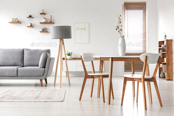 Wooden chairs at table in bright open space interior with lamp n - Stock Photo - Images