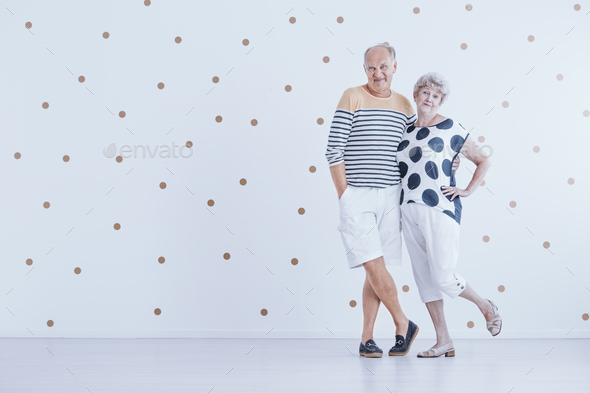 Fashionably dressed senior couple against white wall with gold d - Stock Photo - Images