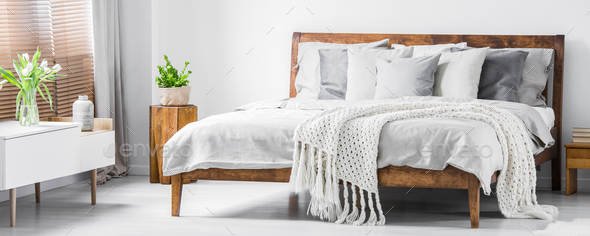 Wooden framed comfortable bed with many pillows, blanket and she - Stock Photo - Images