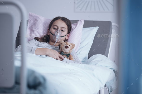 Sick girl with oxygen mask sleeping in a hospital bed with teddy - Stock Photo - Images