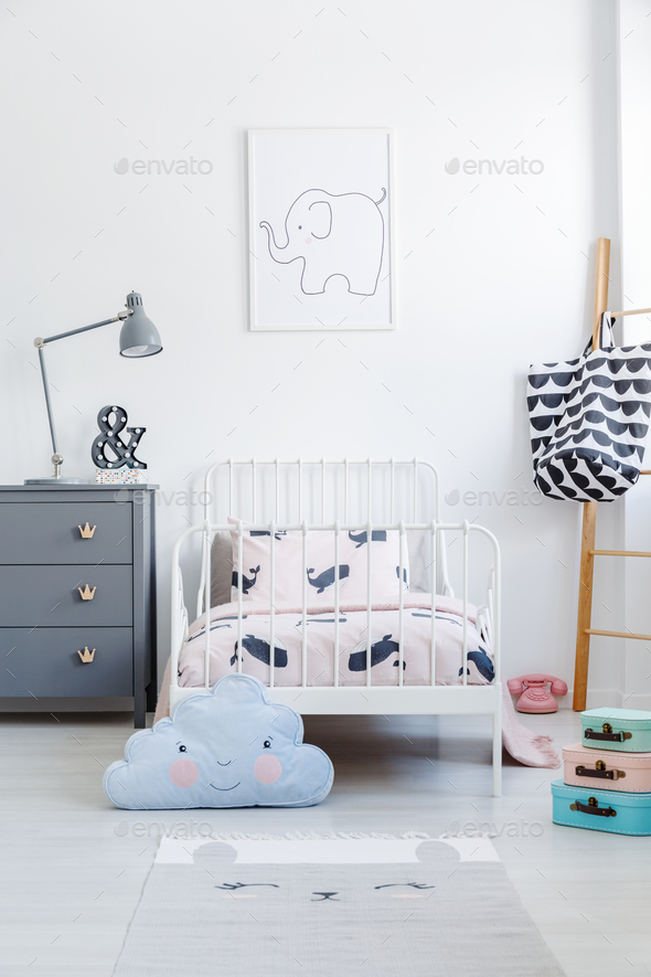 Blue cloud pillow in front of white bed next to grey cabinet in Stock Photo by bialasiewicz