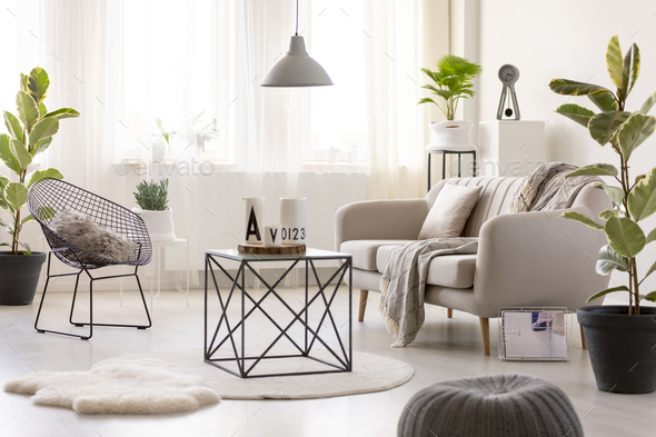 Real photo of a black table standing next to a beige sofa and an - Stock Photo - Images