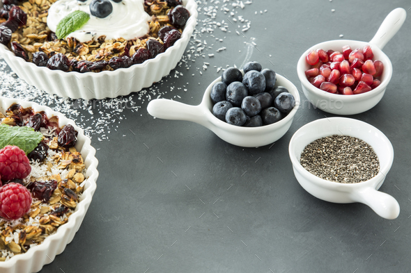 High angle of two bowls of oatmeal with raisins and fruit next t - Stock Photo - Images