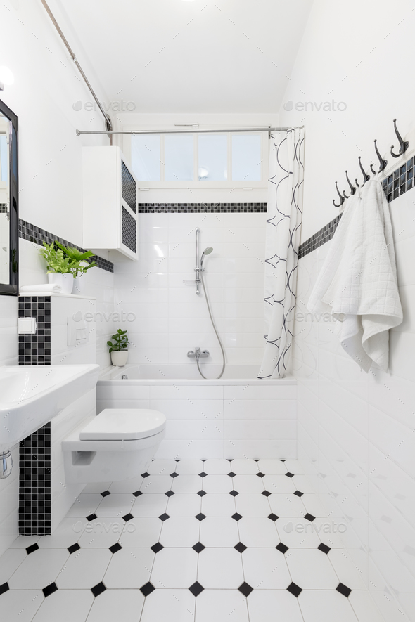 Patterned floor in white and black bathroom interior with towels - Stock Photo - Images