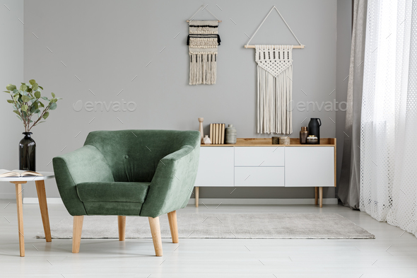 Green armchair in bright boho living room interior with plant on - Stock Photo - Images