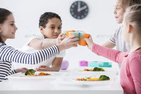 Happy children making a toast during friend's birthday party at - Stock Photo - Images