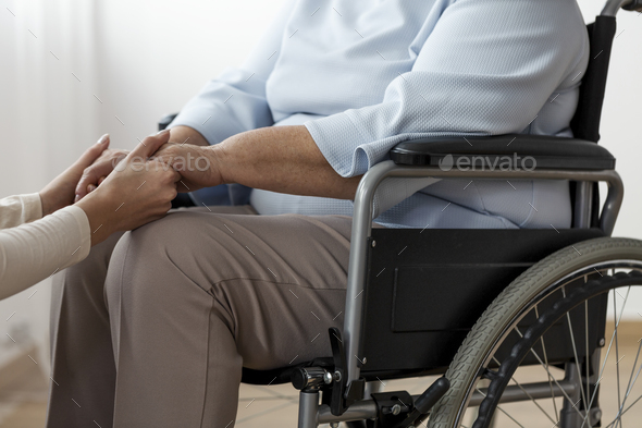 Close-up of a person supporting a paralyzed senior woman in a wh - Stock Photo - Images